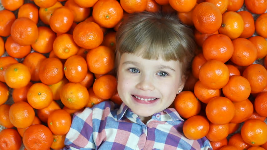 Happy child in oranges. Girl sends a kiss. Top view