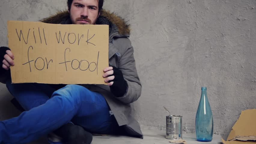 homeless sitting on the floor with a cardboard and a tin