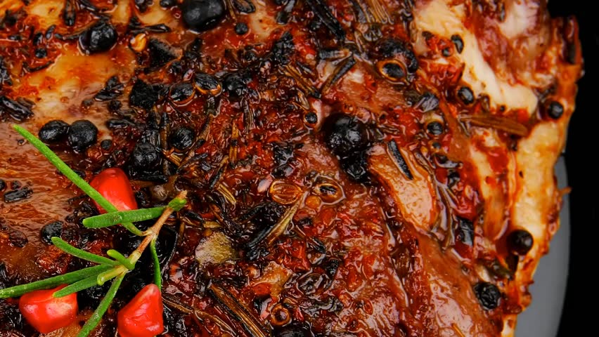 roasted ribs on black plate on wooden table hidef slow motion intro - HD stock footage clip