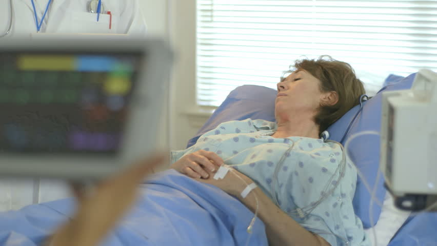 Camera rack focuses from a portable patient monitor held by a doctor to a mature woman lying in a hospital bed. - HD stock footage clip