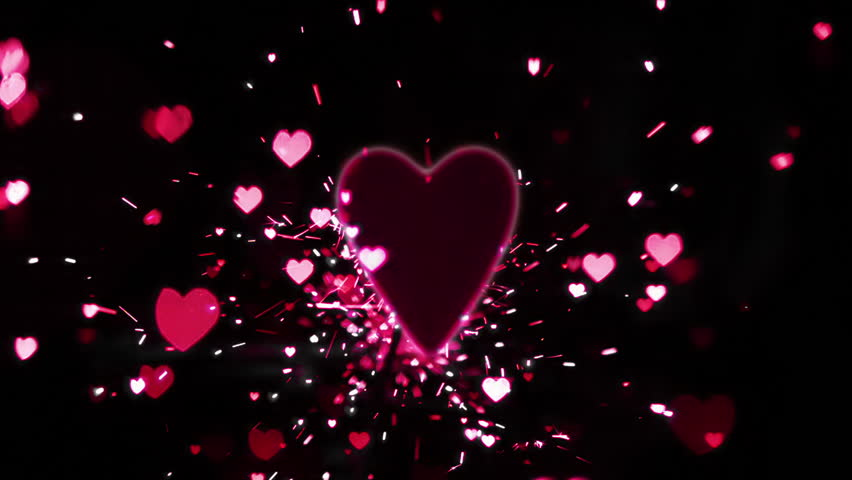 Pink heart confetti and sparks flying against pink heart in slow motion