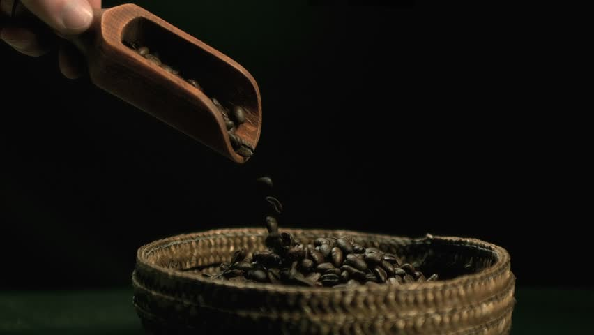 Hand pouring coffee beans from wooden spoon to basket in slow motion