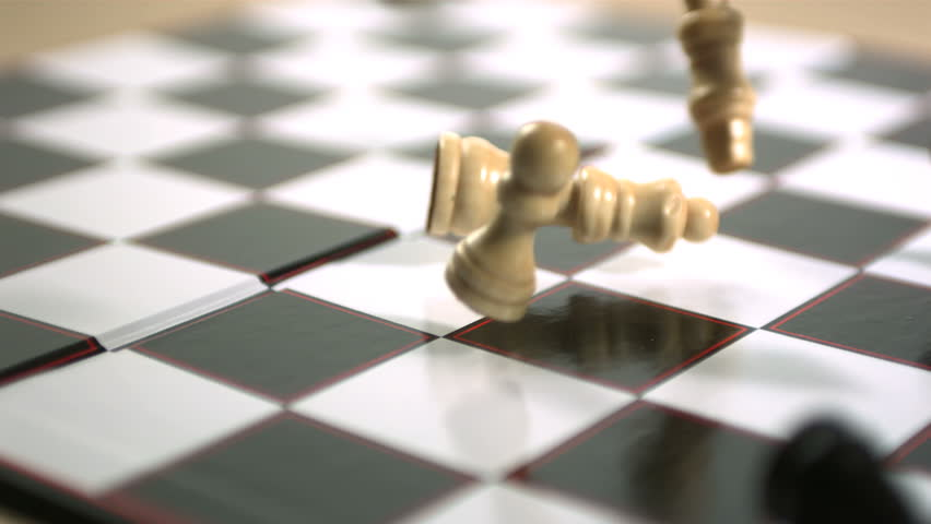 Chess pieces crashing onto board in slow motion