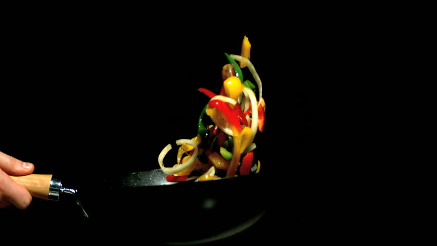Chef tossing vegetables in wok side view in slow motion