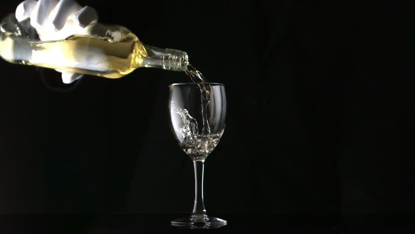 Gloved hand pouring white wine into glass in slow motion