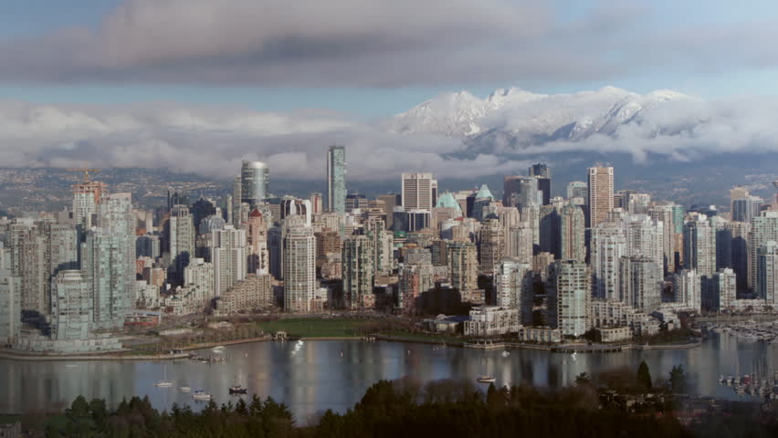 View of downtown Vancouver. Looking north with False Creek in foreground and mountains in the distance. Time lapse. 720P.