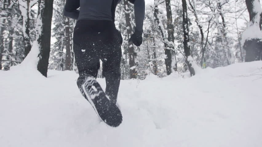 Slow Motion Of Young Sportsman Running Through Snowy Forrest. Shot In The Back.