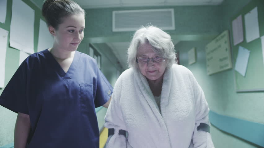 An attractive female medical assistant or nurse helps an elderly lady on crutches to take a walk down a busy hospital corridor. | Shutterstock HD Video #3402284