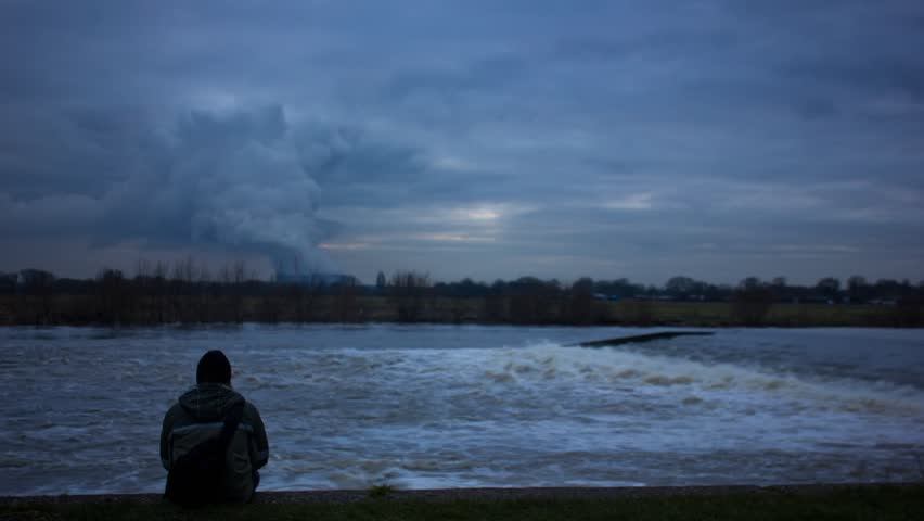 Figure Sitting Infront Of River Rapids And Power Station Timelapse