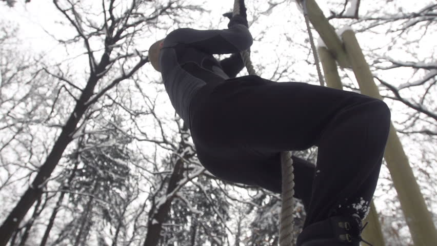Slow Motion Of Young Muscular Sportsman Climbing Up The Rope Outdoors - HD stock video clip