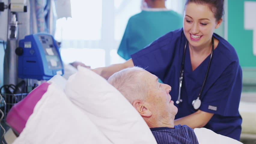 A beautiful female nurse attends to an elderly male patient, plumping up his pillows and chatting with him. | Shutterstock HD Video #3421778