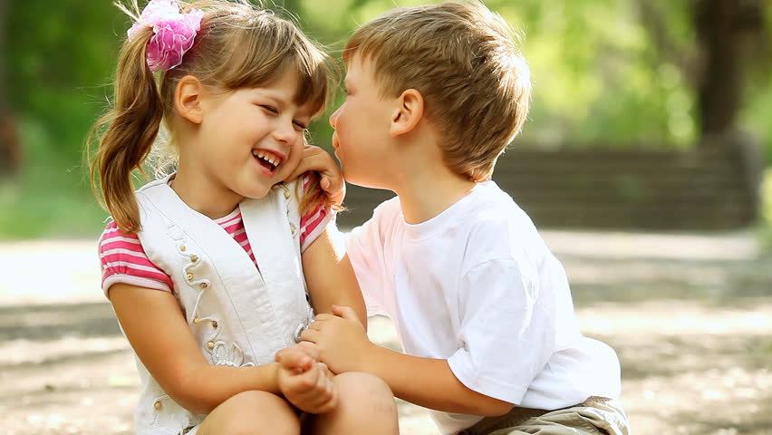 Two children telling secrets and laughing in park, outdoors. dolly shot. - HD stock footage clip