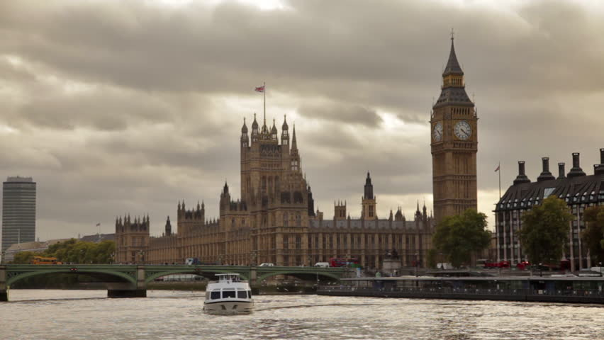 Dark storm clouds behind Big Ben and Westminster palace, Thames river, flying