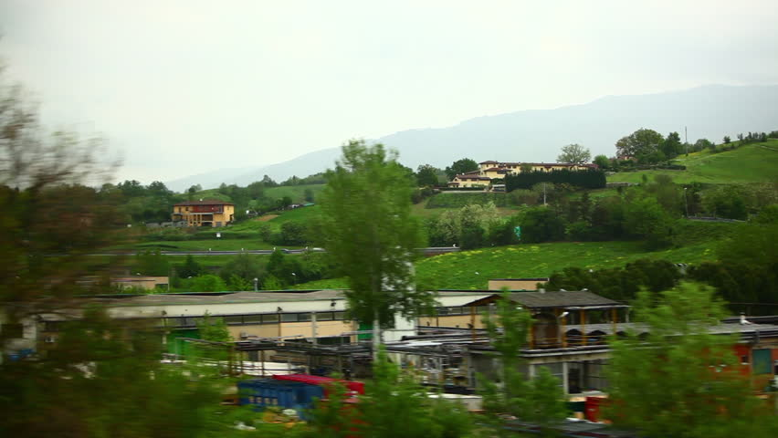 A tracking shot of warehouses and countryside in Italy captured during a train