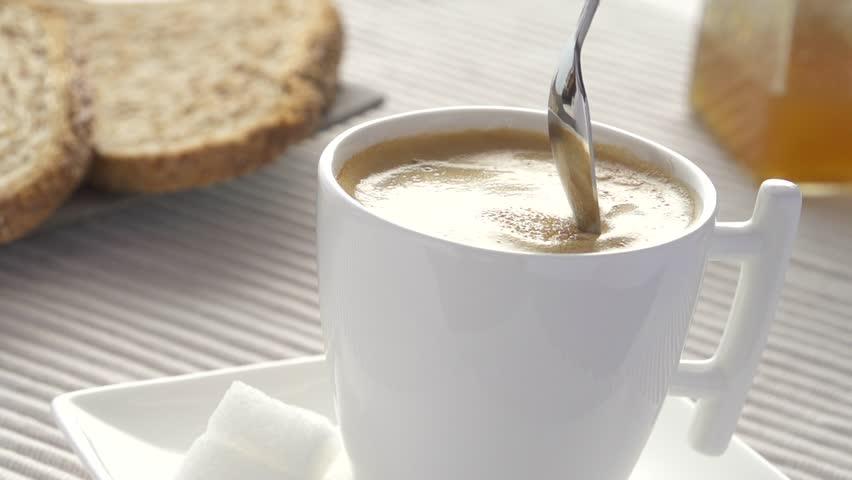 Slowmotion adding sugar in coffee and stirring