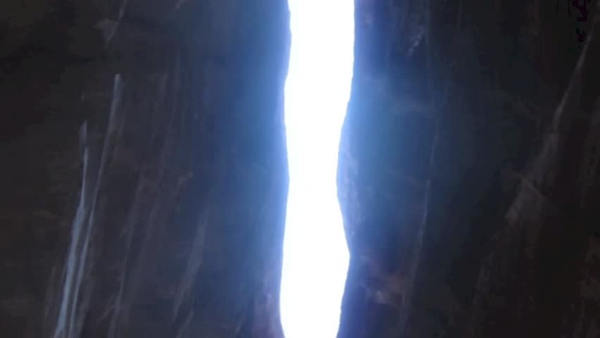 The Siq, the narrow slot-canyon that serves as the entrance passage to the hidden city of Petra, Jordan, seen here with tourists walking.This is an UNESCO World Heritage Site - HD stock footage clip