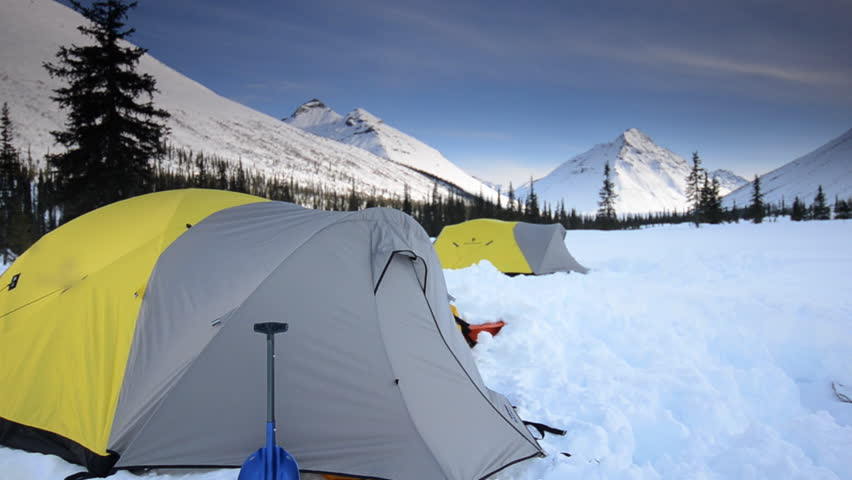A view of two tents set up in the snow at sunset in the Alaskan wilderness