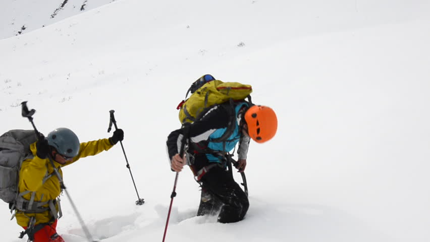 A group of mountain climbers with backpacks full of gear hike along a snow covered mountain side in the Alaskan wilderness