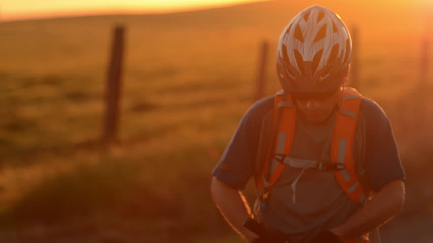 A photographer takes pictures of a mountain biker riding past him on a trail in a field during the day at sunset