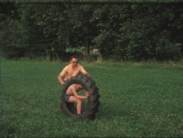 Vintage 8mm film: Boy in tire rolled by father, 1970s - HD stock video clip