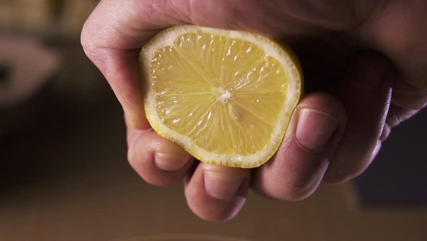 hand squeezing lemon on dark background