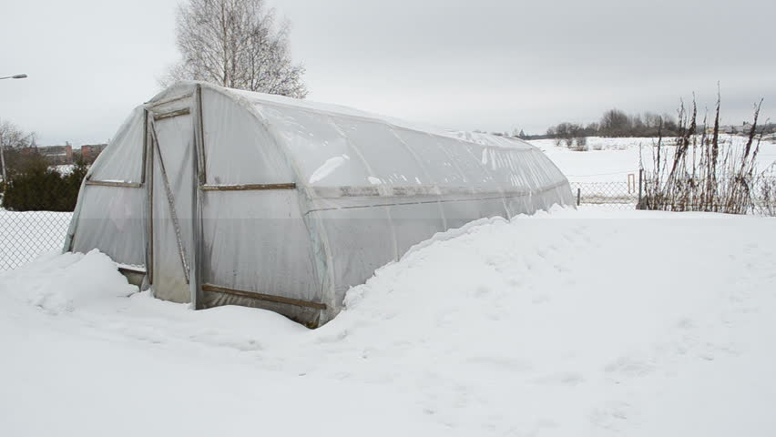 panorama view of wooden diy homemade greenhouse covered with polythene and snow in winter garden. snow falling. - HD stock footage clip