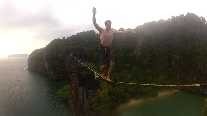 A brave and adventurous climber walks across a slackline over a bay in a tropical setting, with the ocean and jungle behind him, during the day | Shutterstock HD Video #3475661