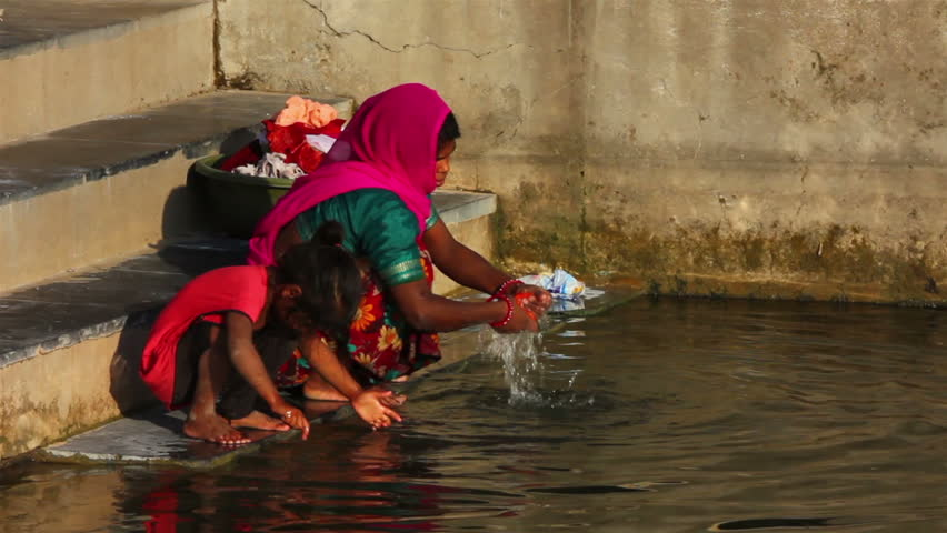 UDAIPUR, INDIA - NOVEMBER 24, 2012: Indian woman washing clothes in the lake in Udaipur, India, 24 nov 2012 - HD stock footage clip