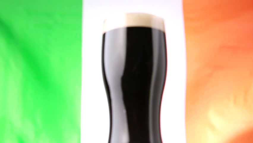 Pint of stout against irish flag blowing in the wind