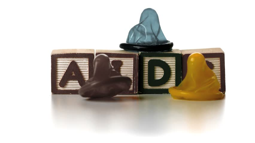 Three condoms falling on blocks spelling AIDS in slow motion - HD stock video clip