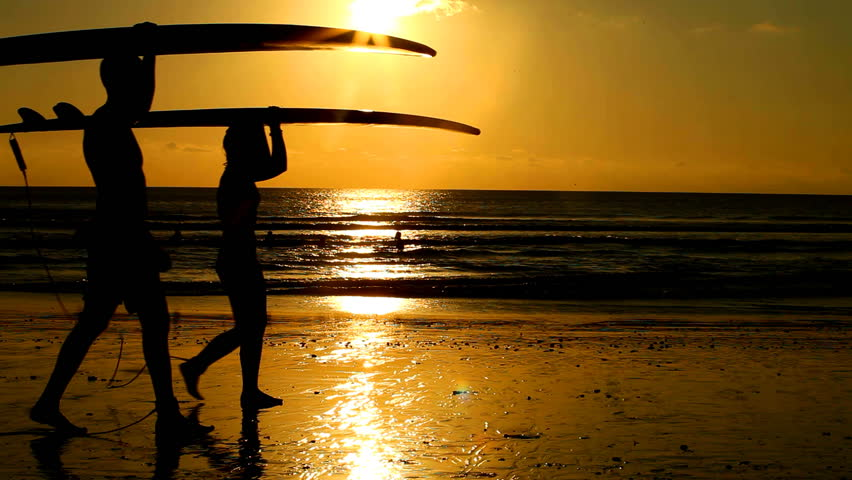 Surfer couple in silhouette walking with long surf boards at sunset on tropical beach - HD stock footage clip