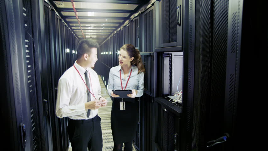 Three people of mixed ethnicity are working in a data center with rows of server racks and super computers. They are walking up and down and checking all of the equipment.