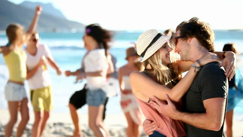 Hipster Friends having fun at the beach and a couple kissing in the front.  - HD stock footage clip