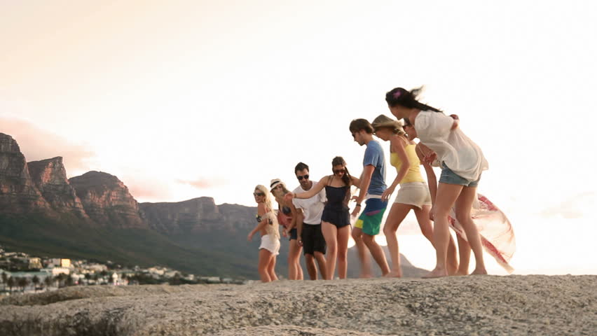 Young fun party hipster people  dancing on a rock at the seaside. - HD stock footage clip