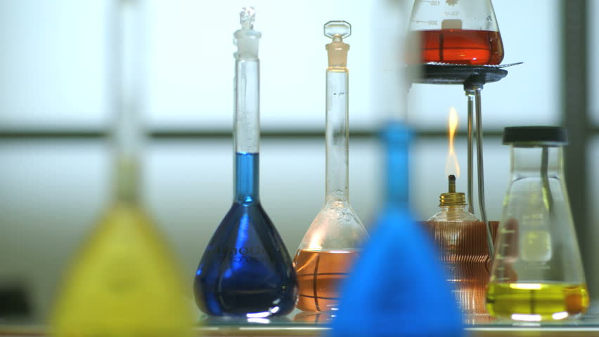 Slight movement to the right across a flame from an alcohol burner and volumetric flasks filled with colorful liquid. - HD stock footage clip