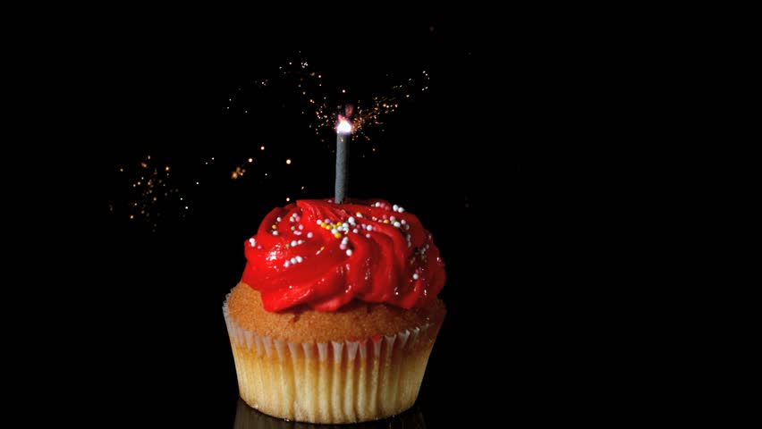 sparkler burning on red birthday cupcake in slow motion