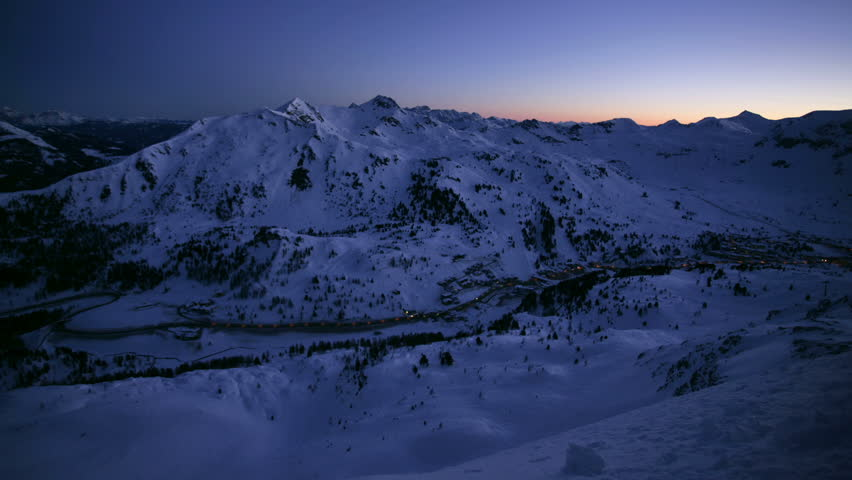 time lapse 24 hours in snow covered mountains with blue sky at daytime and lights during night
