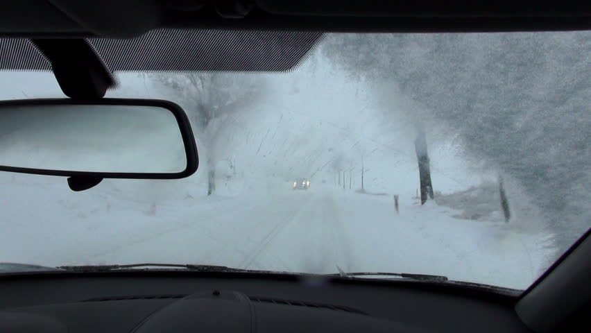driving by car in real winter conditions, view from inside out on snow covered street. pov.