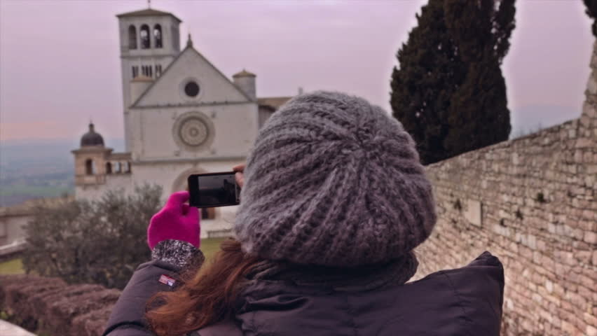 Woman taking pictures with smartphone to a church in her trip to Europe.