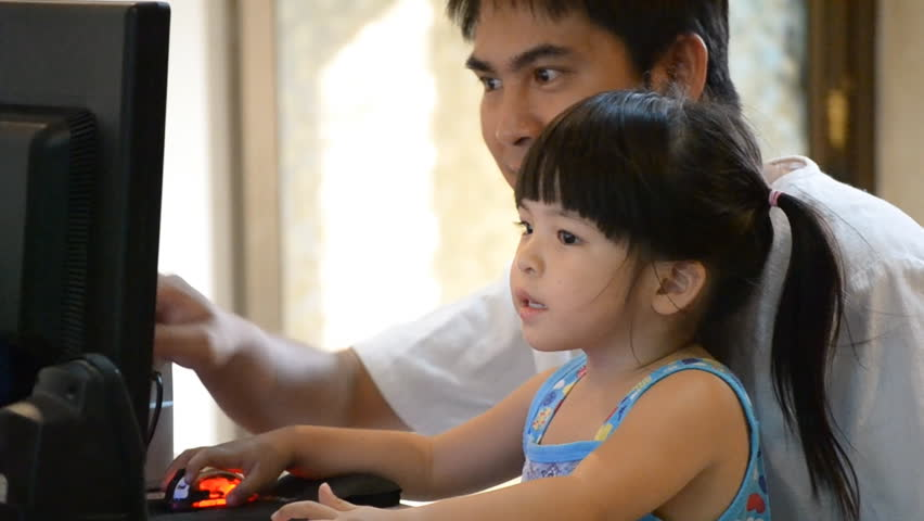 asian father teach cute daughter use computer
