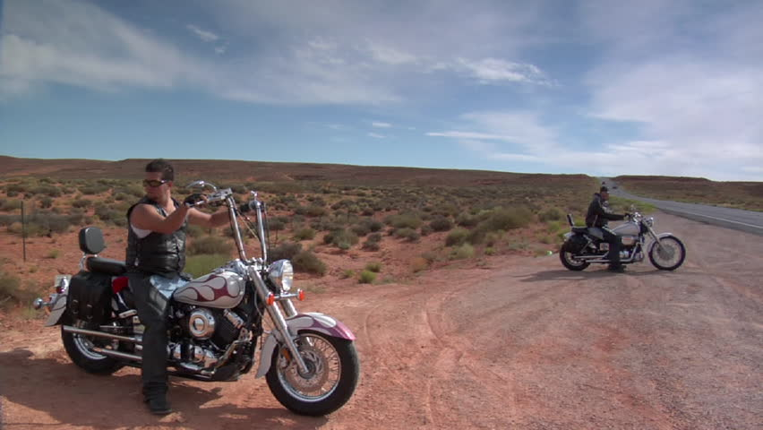 Motorcyclists resting on side of desert road - HD stock footage clip