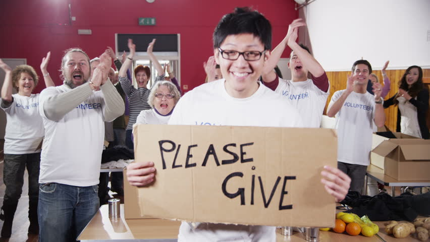 "A male charity volunteer of Asian ethnicity holds up a ""Please Give"" sign and smiles at the camera as his fellow volunteers applaud and cheer in the background. In slow motion. - HD stock video clip"