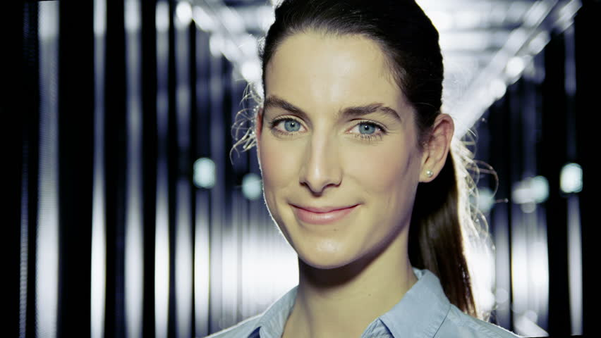 Portrait of a female IT engineer who is working in a data center with rows of server racks and computers.  #3589277