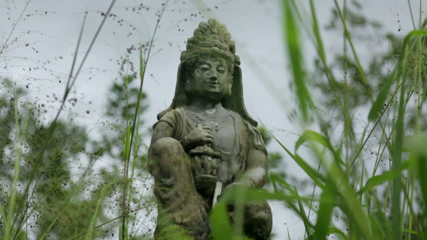 A stone statue of the Hindu goddess Shiva sits serenely amidst tall blades of green grass blowing in the breeze. - HD stock footage clip