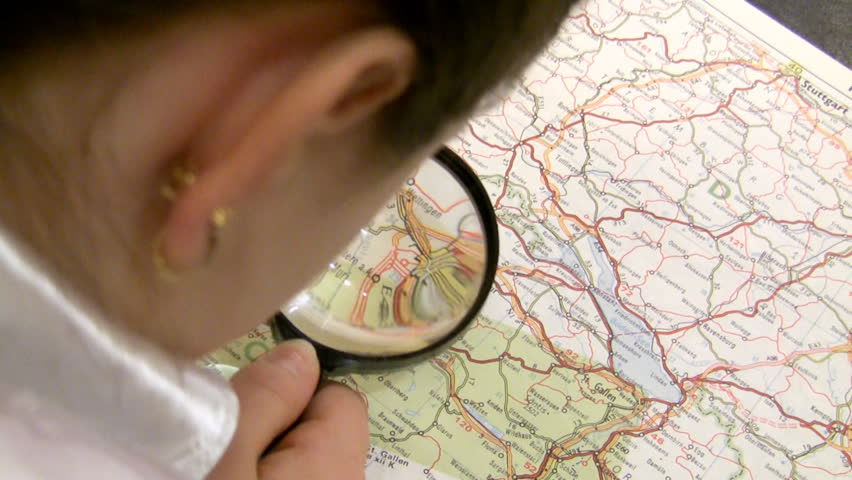girl with a magnifier studies a map of Europe.  - HD stock footage clip