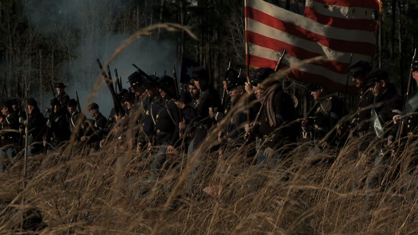 FLORIDA - FEBRUARY 2013 - large-scale, epic Civil War anniversary reenactment -- in the middle of battle.  Smokey Battlefield as Union Infantry advances into battle with flag flying in tall grass.