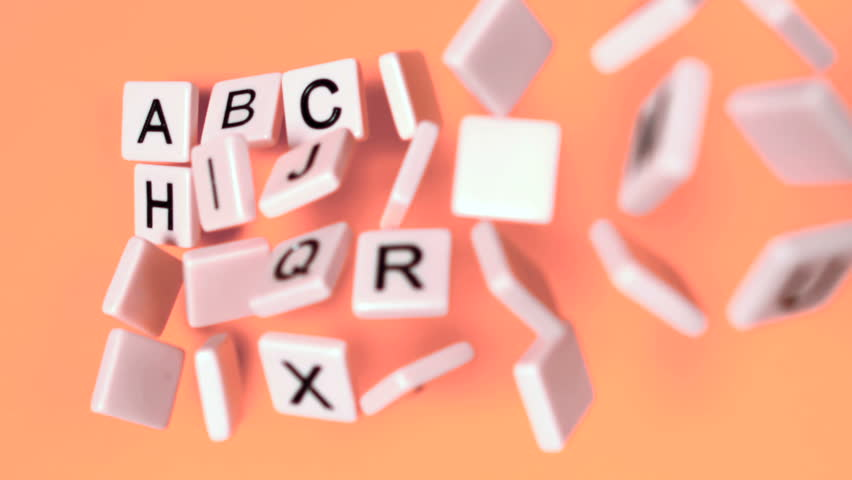 Plastic letters bouncing and showing alphabet on orange surface in slow motion - HD stock footage clip
