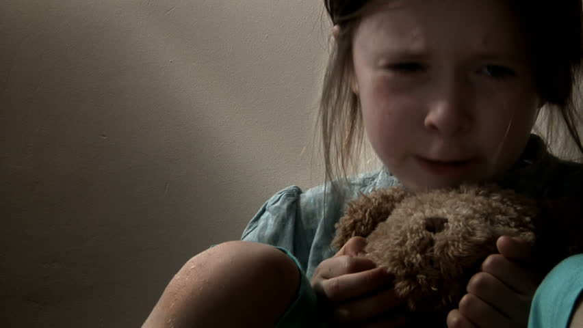 Little girl crying, with tears streaming down her face, clutching her teddy bear. Intentionally desaturated.