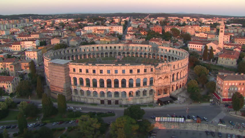 A circling view of the Arena of Pula at sunset. Aerial helicopter shot.