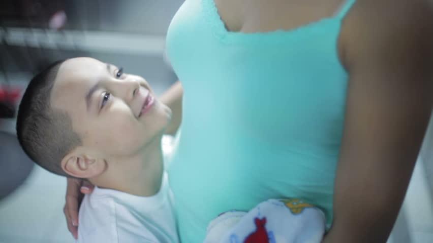 Handsome spanish little kid embracing mother